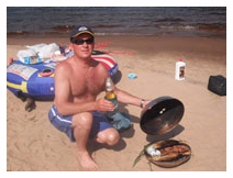 Captain John Wagner grilling the catch on the beach